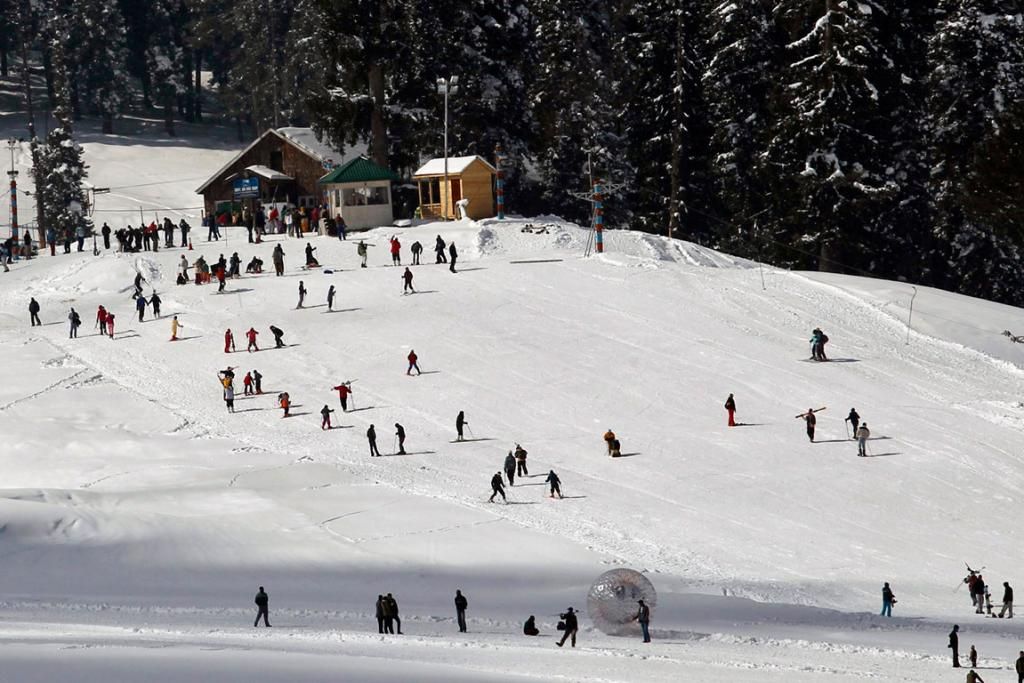 Tourists and skiers ski on a slope in Gulmarg,