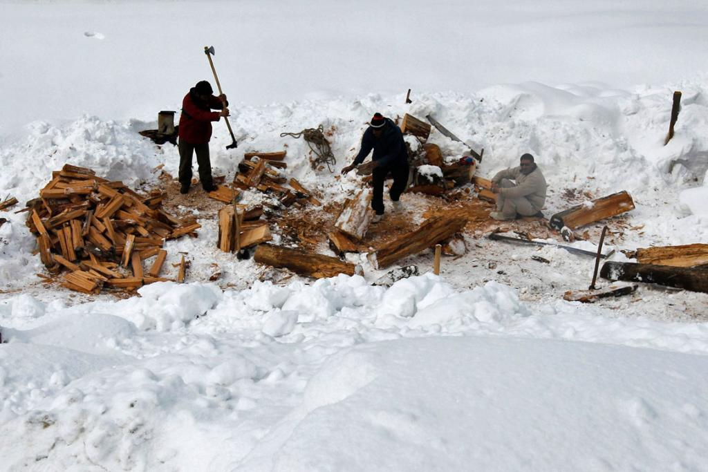 Kashmiri men cut firewood for a hotel in Gulmarg.
