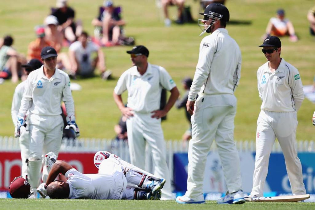 Kieran Powell hits the deck after being hit by a delivery, as New Zealanders look on.