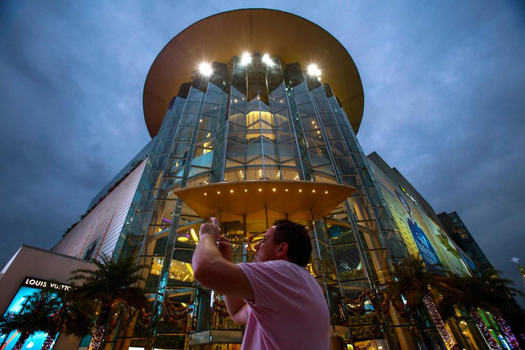 A tourist takes a photo in front of Siam Paragon Department Store in central Bangkok.