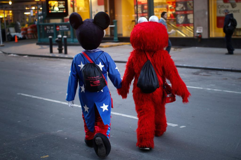 Costumed characters dressed as Mickey Mouse and Elmo who collect tips by posing with tourists in and around Times Square hold hands as they cross a street in midtown Manhattan in New York City.