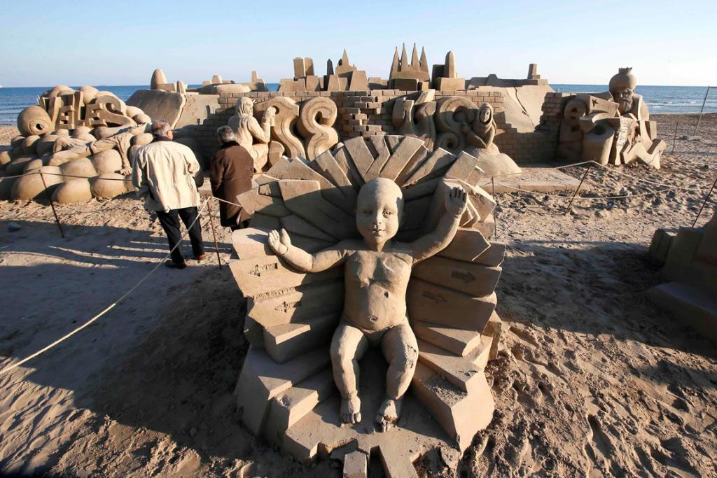 People walk in a nativity scene made of sand on a beach in Salou, Spain.