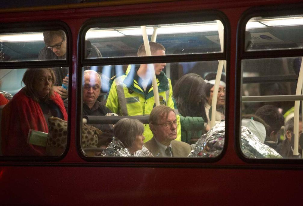 People receive medical attention on a bus after part of the ceiling at the Apollo Theatre