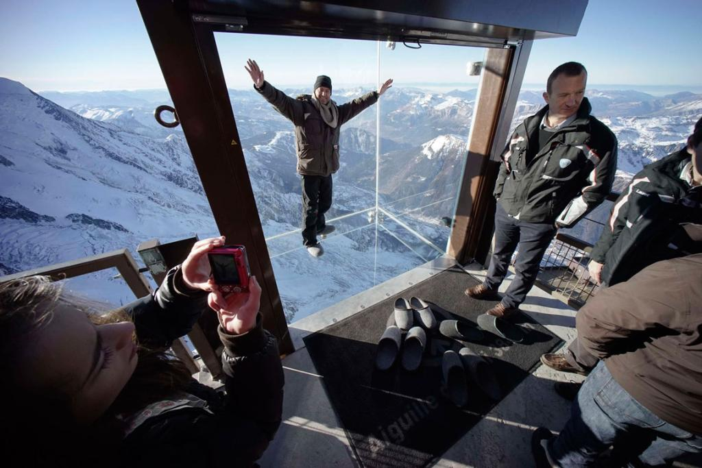 Journalists and employees, wearing slippers to protect the glass floor, visit the 'Step into the Void' installation as they attend a press visit at the Aiguille du Midi mountain peak above Chamonix, in the French Alps.