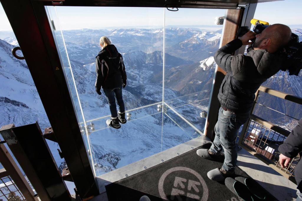 Journalists and employees, wearing slippers to protect the glass floor, stand in the 'Step into the Void' installation.