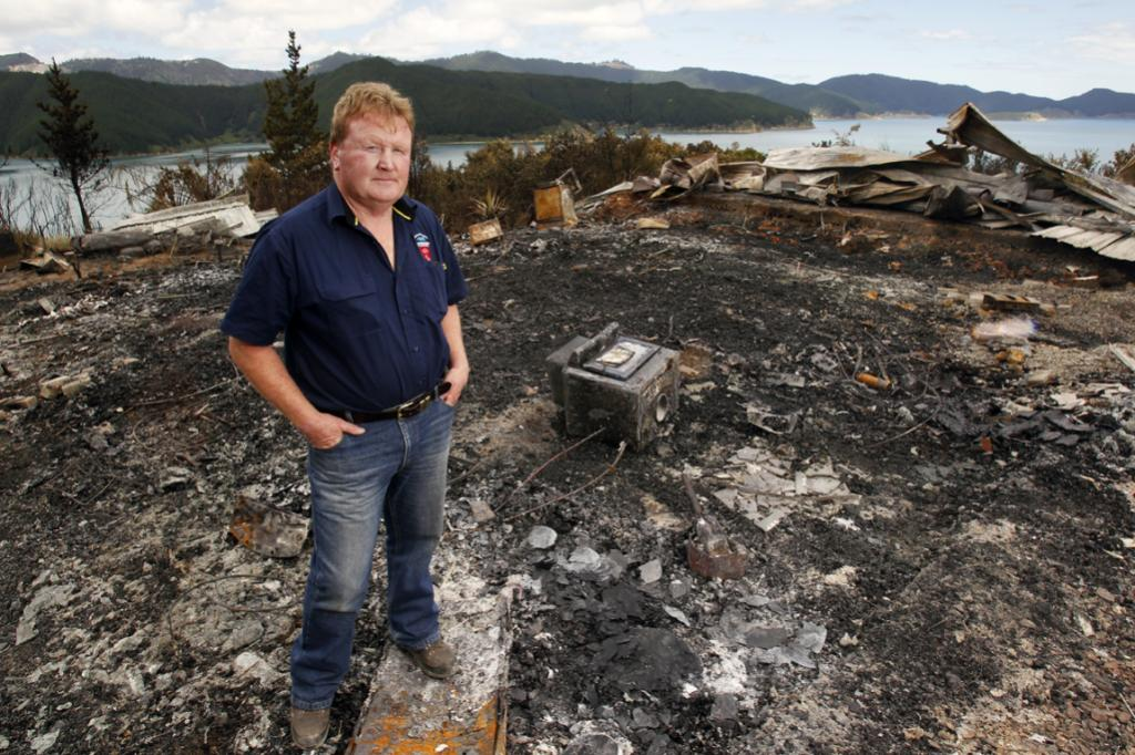 Marlborough rural fire chief Richard McNamara inspects the wreckage of a home destroyed in Saturday's fire.