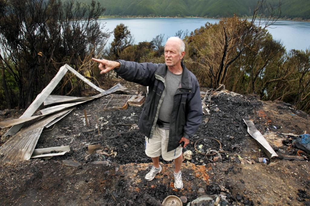 Port Underwood resident Bob Archer inspects the damage caused by the fire at the weekend.