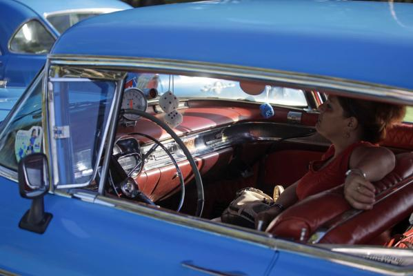A participant sits in a car during the annual classic car exhibition in Havana.