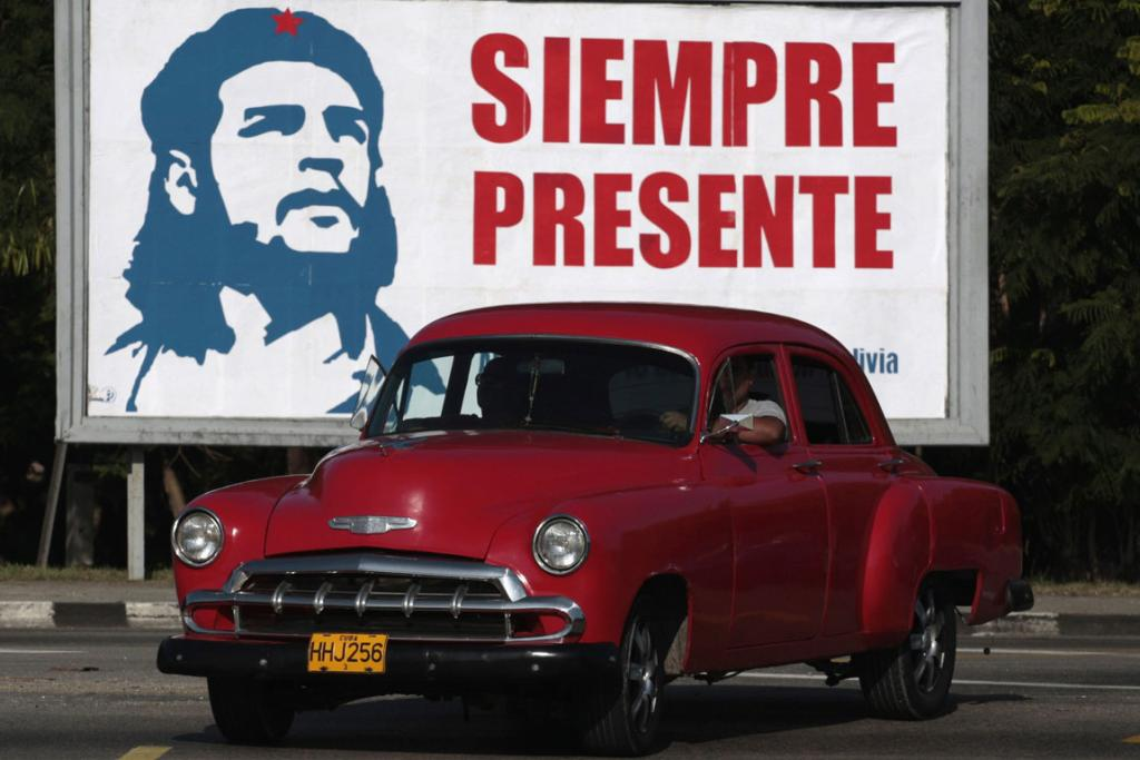A car is driven beside a billboard with the image of revolutionary leader Che Guevara in Havana October 8, 2013.