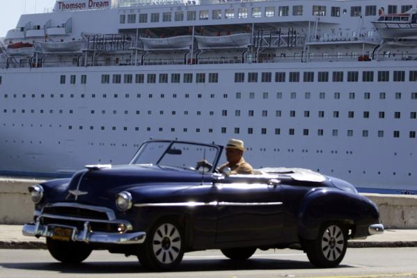 A man drives his convertible car beside the Maltese flagged ''Thomson Dream'' cruiser docked at Havana's port December 6, 2013.