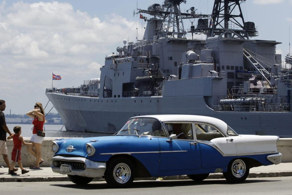 A car drives past a Russian army warship docked at Havana Port August 3, 2013.