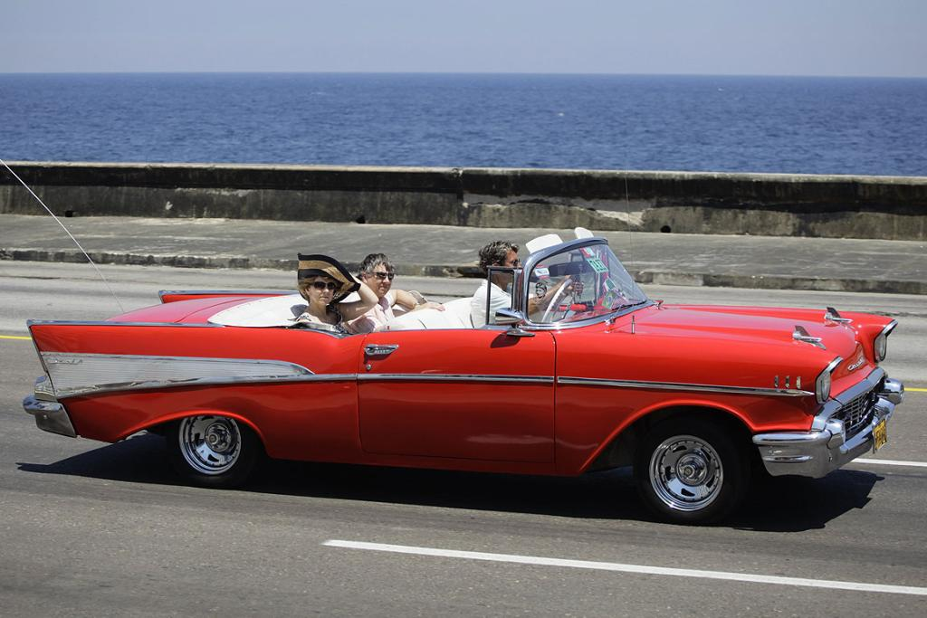 """Tourists ride a US-made 1957 Chevrolet Bel-Air convertible car on Havana's seafront boulevard """"El Malecon"""" May 21, 2013."""