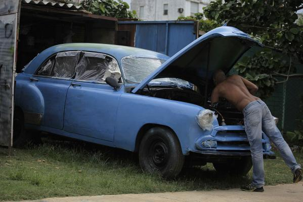 A man works to restore his 1950's US-made car at a garage in Havana June 30, 2013.