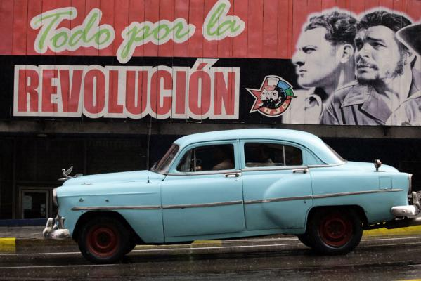 A US-made car, used as a private collective taxi is driven beside a billboard in Havana September 30, 2013.
