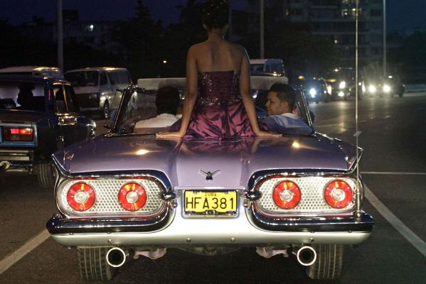 A girl rides on the back of a vintage convertible car, as part of her quinceanera (coming-out for 15-year-olds) celebration, in Havana August 25, 2013.