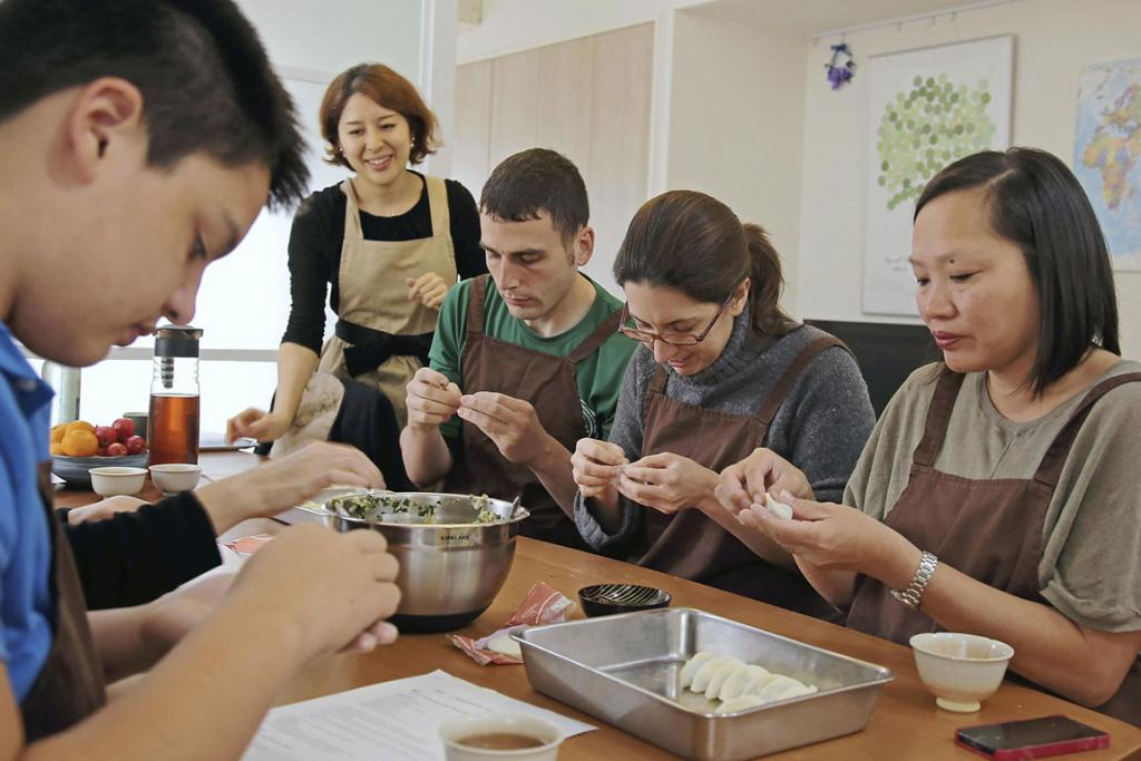 Students attending a cooking class at Mari Nameshida's home in Tokyo make Japanese-style gyoza dumplings. Although gyoza are originally from China, they are now a popular home dish in Japan.