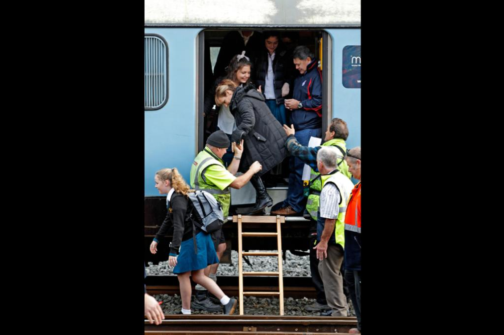 Sudden stop: Commuters are helped off the derailed train carriage.