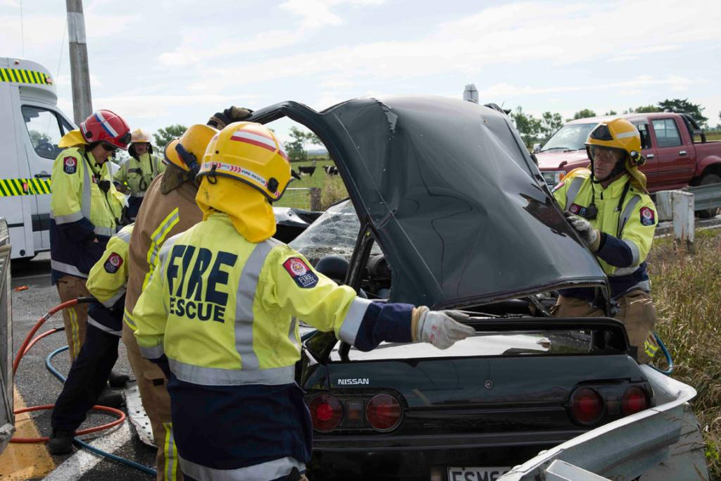CAR CUTTING: Firefighters work to free a man trapped in his car following a collision with a van.