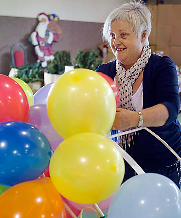 FESTIVE: Volunteer Maureen McCarthy prepares balloon decorations for the City Mission lunch.