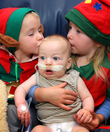 THAT'S THE SPIRIT: The Howard family spent Christmas in hospital but they didn't miss out on Christmas cheer. George, 3, and Meg, 5, kiss their younger brother Jack, 4 months, in the Southland Hospital children's ward.
