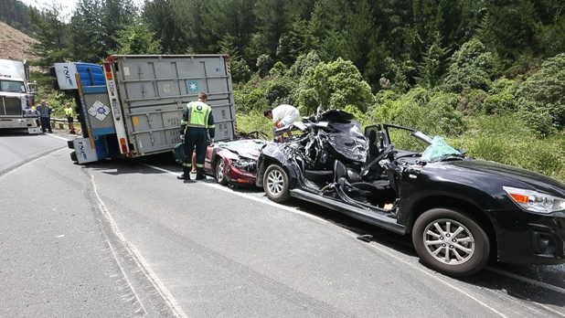 Miracle: Belinda Vavasour was cut from the black car after it was squashed by the truck and trailer on State Highway 6.