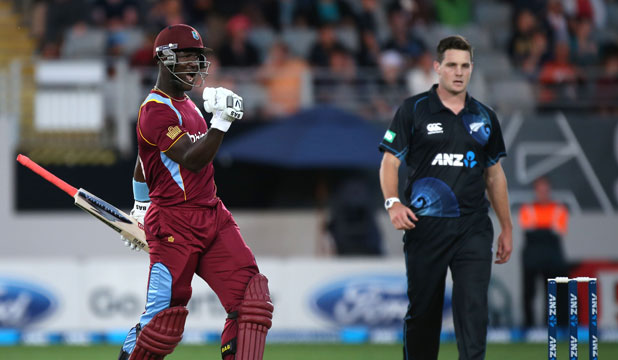 Darren Sammy celebrates after hitting the winning runs, while a dejected Mitchell McClenaghan looks on.