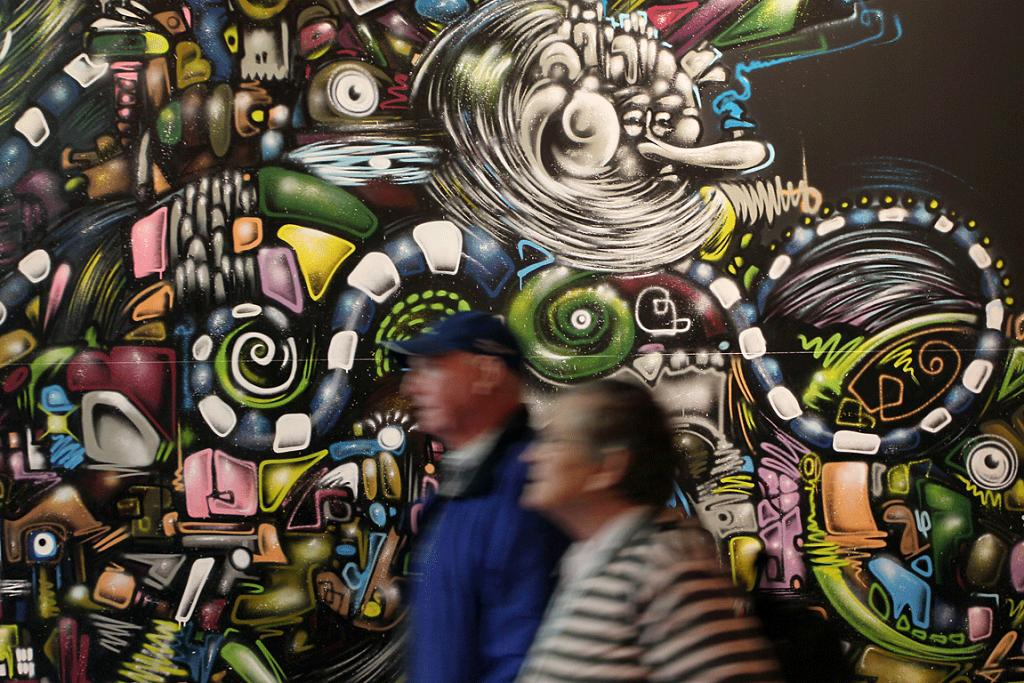 THE PAINTING'S ON THE WALL: People walk past street art as part of the RISE exhibition at Canterbury Museum.
