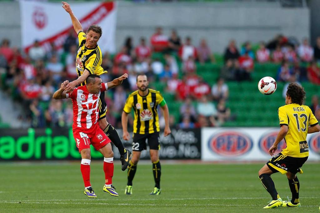 Ben Sigmund leaps over Michael Mifsud to head the ball away.