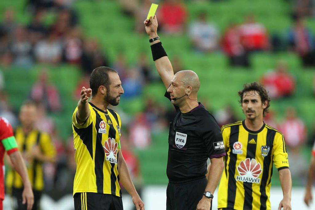 Andrew Durante is shown a yellow card by referee Strebre Delovski.