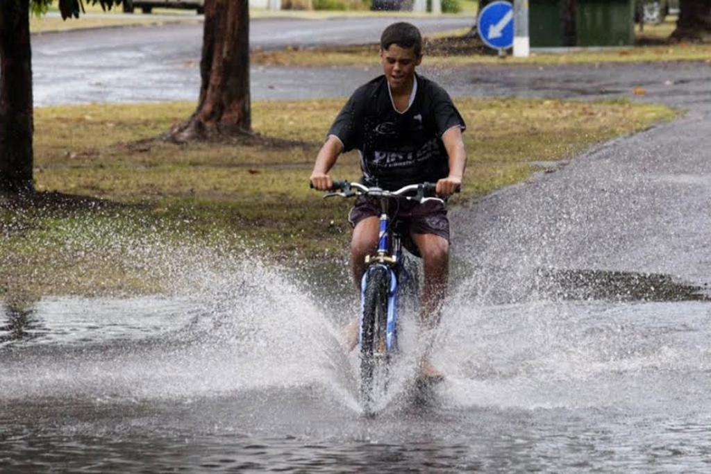 Jacob Gordon rides through the Pauanui Beach flood waters.
