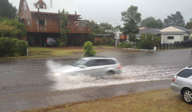 AWASH: A car drives along a flooded road in Pauanui in the Coromandel.