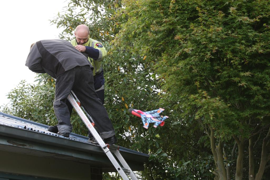 Richard Goodger is helped down from his roof by emergency services personnel after he climbed up to rescue his son's toy.
