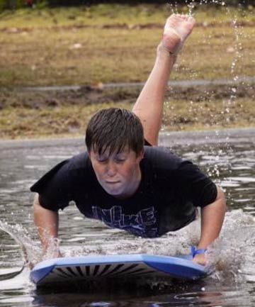 WET FUN: Luke Taylor finds a quick way to negotiate the flooding at Pauanui Beach.