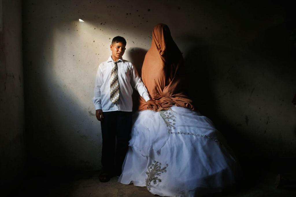 Ahmed Soboh, 15 and his bride Tala, 14, stand inside Tala's house which was damaged during an Israeli strike in 2009, during their wedding party in September, 2013.
