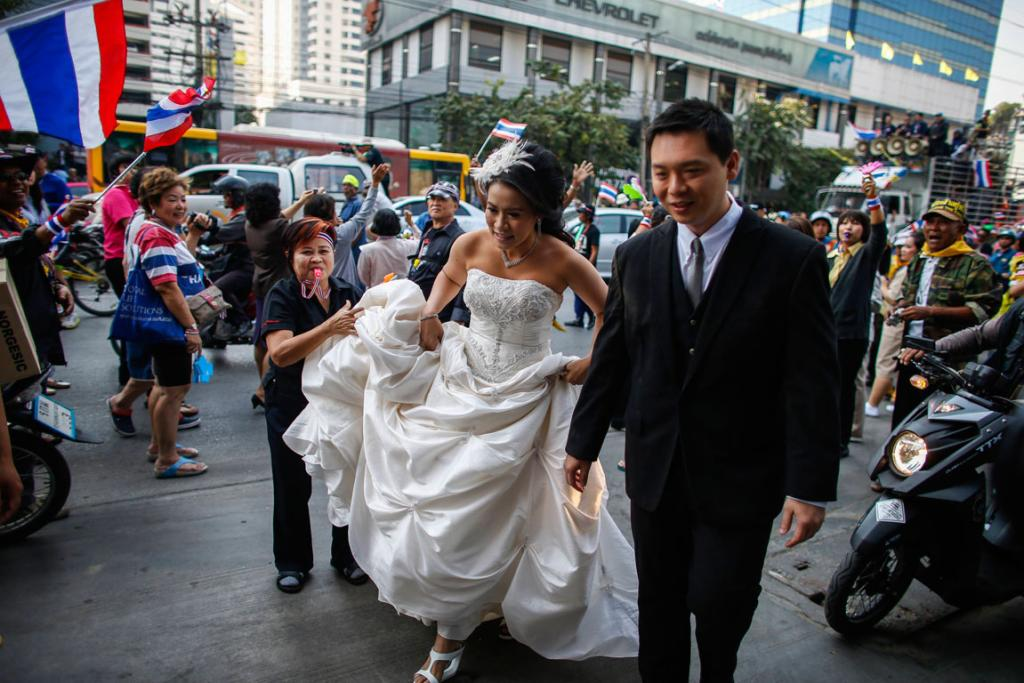 A bride and a groom arrive to take pictures ahead of their wedding as anti-government protesters march during a rally in Bangkok, December 2013.
