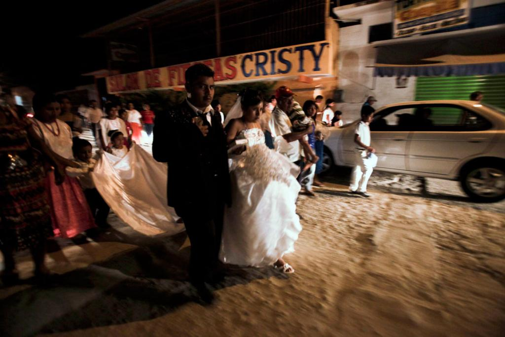 Newlyweds walk down a street in the Mexican town of Ayutla de los Libres, weeks after police and locals took up arms against organised crime gangs in January 2013.