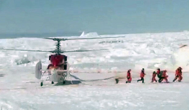 Rescue workers make their way from a helicopter to the Russian ship Akademik Shokalskiy