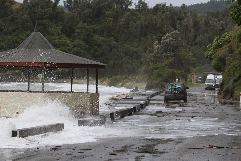 High tide and wild weather drive the sea over the road at Pohara, Golden Bay.