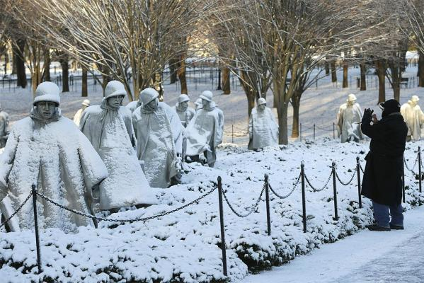 A man photographs the Korean War Veterans Memorial after a heavy snow storm in Washington DC on January 3, 2014.