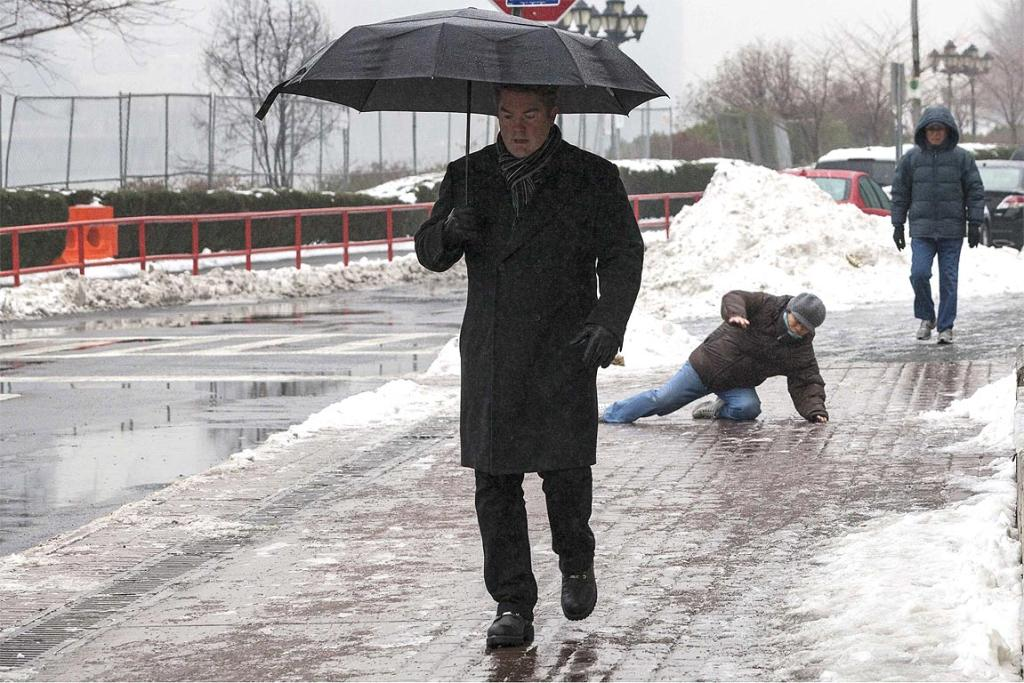 A man falls while slipping on ice during freezing rain on Roosevelt Island, a borough of Manhattan in New York.