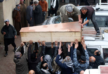 Mourners carry the coffin of a soldier killed during clashes in Falluja, at his funeral in Najaf on Sunday.