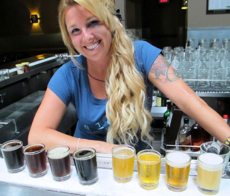 Bartender Leah Mark serves up tasting flights on the frosted counter at Maui Brewing's brew pub in Hawaii.