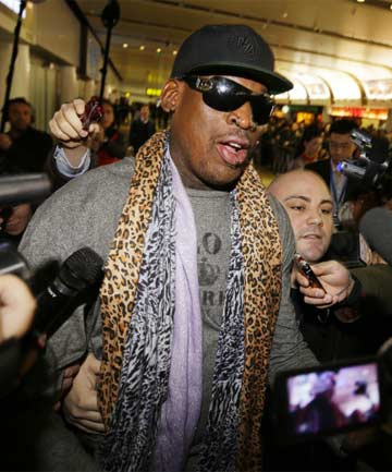 STAYING QUIET: Dennis Rodman is accosted by reporters on his arrival in Beijing.