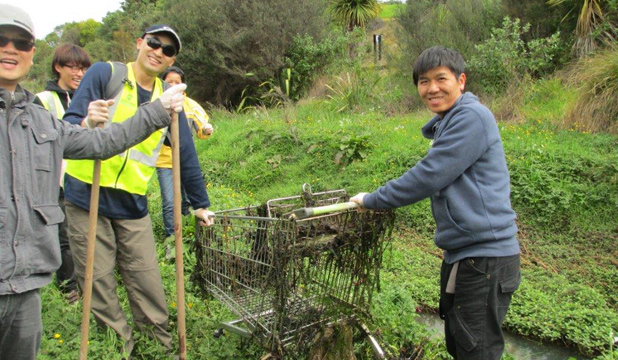 TRASH REMOVED: Members from the Light & Love Home New Zealand church pull a trolley out of the Pakuranga Stream.