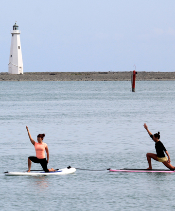 ON BOARD: Jane Pascoe, left, and Linda Brownie take a yoga paddle board class at Port Nelson.