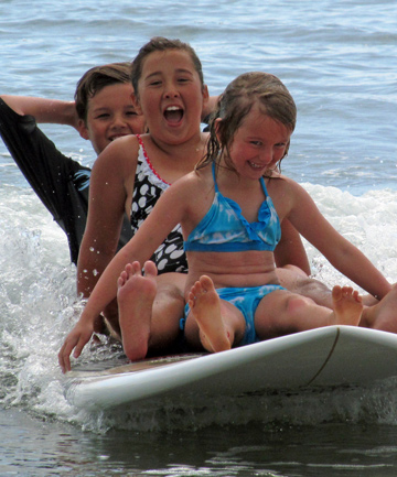 COOLING OFF: Popular beaches were packed on January 2. These youngsters having fun on a stand up paddleboard at Orewa beach can expect more days in the surf escaping the heat.