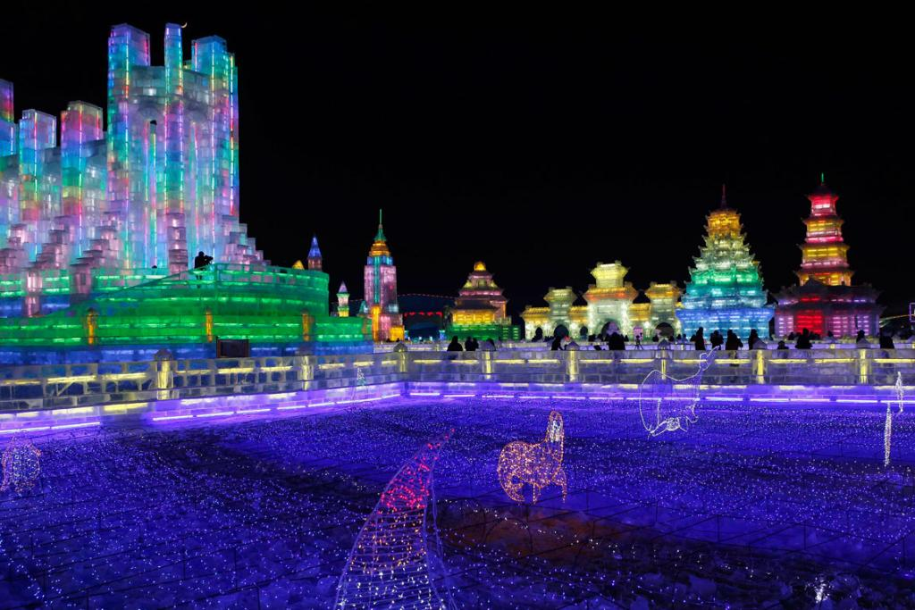 Visitors look at ice sculptures during a light-up rehearsal ahead of the Harbin Ice and Snow Sculpture Festival.