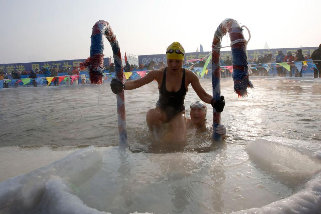 Swimmers climb out of a pool carved into the thick ice covering the Songhua River.