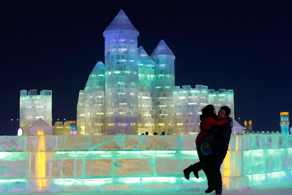 A couple shares an embrace in front of an ice sculpture.