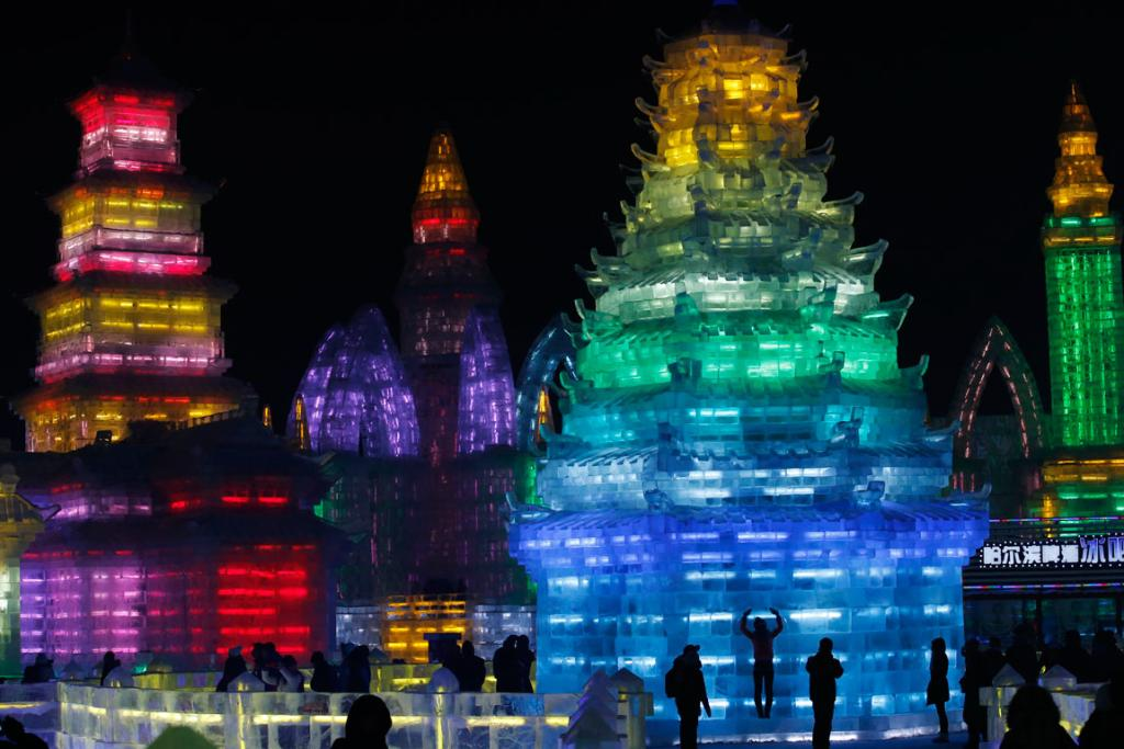 Visitors are silhouetted against lighted ice sculptures at the Harbin Ice and Snow Sculpture Festival.